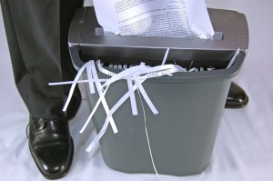 Man's Feet Standing Next to Shredder with Document In Process of Shredding